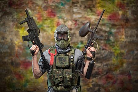 gamer: Handsome paintball gamer with guns in camouflage uniform