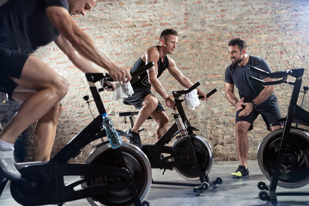 Young sporty man with personal trainer on spinning class