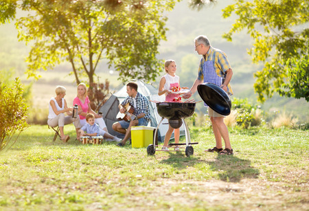 kleindochter helpen grootvader grillen voor familie Stockfoto