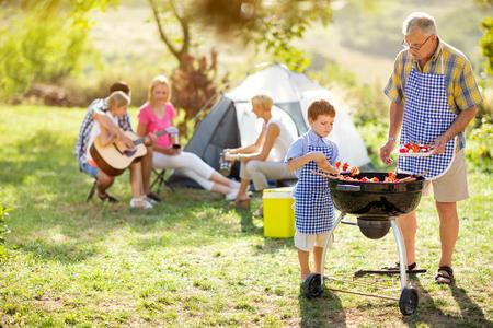gelukkig gezin op de camping maken barbecue Stockfoto