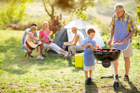 glückliche Familie auf Camping Herstellung Grill