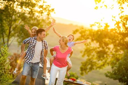 Ouders en kinderen op vakantie samen spelen buiten