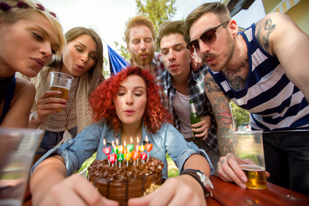 chocolate birthday cake: Birthday girl blows candles on chocolate birthday cake with friends