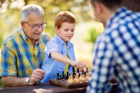 Junge spielt Schach auf dem Tisch im Park Standard-Bild