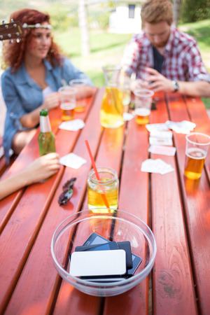 postponed: Youth postponed their mobile phones in glass bowl on wooden table outdoor