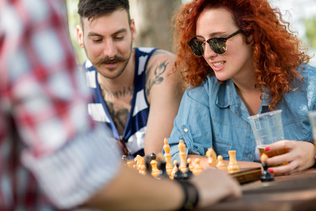 ginger haired: Curly ginger haired female plays chess with male friends at camp in nature