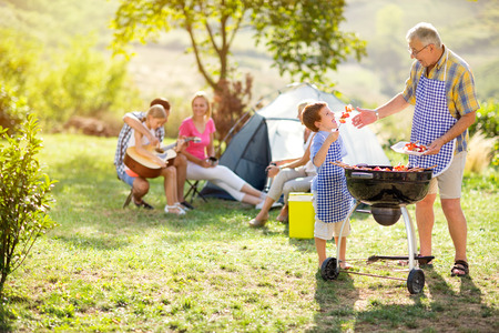 grandfather and grandson making barbecue for family