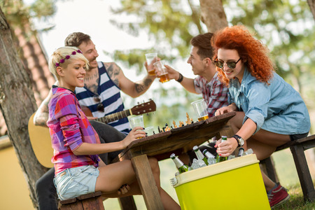 refreshes: Ginger woman takes out cold beer from green picnic handheld refrigerator