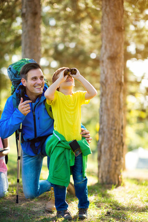 Father and son looking through binoculars in nature Stock Photo