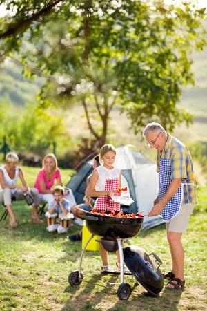kleindochter en grootvader op de barbecue op camping Stockfoto