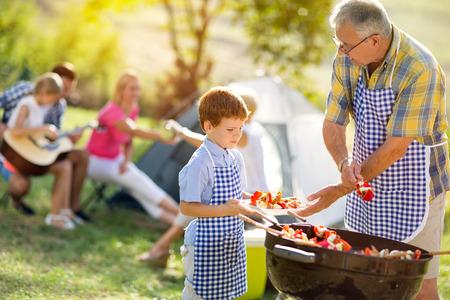 Großvater geben Enkel grillied Fleisch für das Abendessen