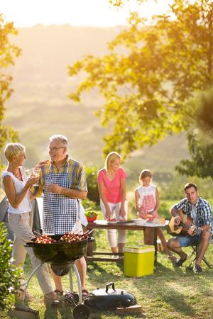 parrillero: sonriendo abuelos bebiendo vino y disfrutando de picnic con la familia Foto de archivo