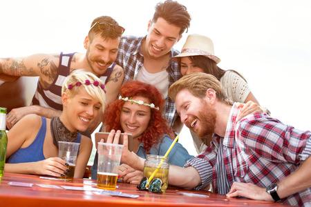 Groupe de jeunes amis regarde quelque chose de mignon sur le téléphone mobile dans la nature Banque d'images