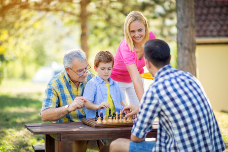 patience: family relax time playing chess in nature