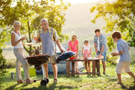 Happy family camping and cooking bbq
