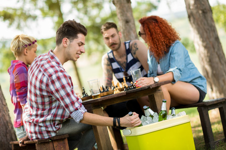 refreshes: Guy on picnic in forest takes out cold beer from handheld refrigerator