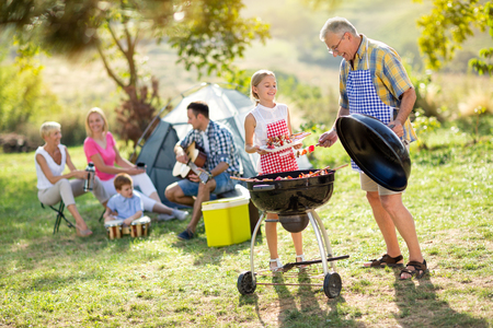 family together: happy grandfather and granddaughter making barbecue for family