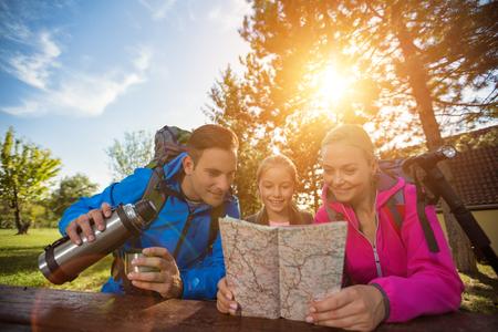 familie met rugzak in bos met kaart