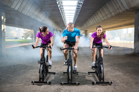 to spin: exercising fit people on spin bike outdoor Stock Photo