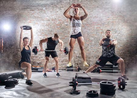 pesas: pesos de la gente del entrenamiento deportivo activos, entrenamiento de elevación