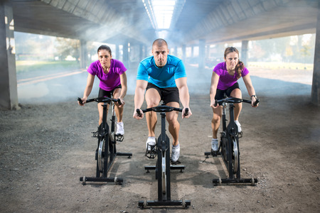 sports people training bike riding on exercise bicycle Stock Photo