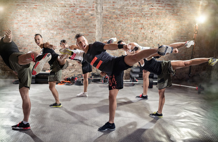 female boxing: Group of young people  doing kick box exercise, expressing aggression Stock Photo