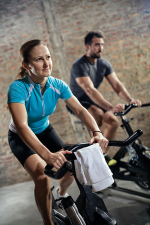 to spin: Sporty fit couple in sports clothing doing training on bicycle