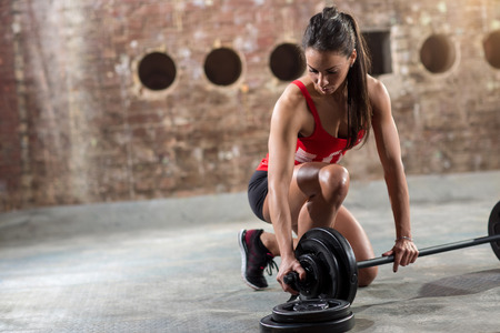 prepare: sexy young fitness woman preparing to lift some heavy weights