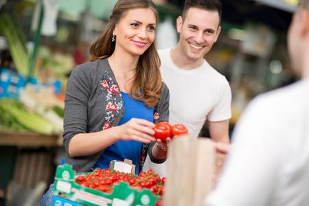 street market: young couple buying cherry tomato at street market Stock Photo