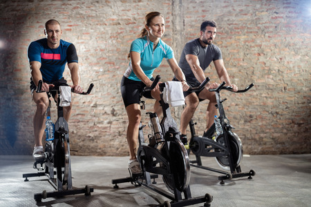 to spin: Young people cycling workout with rhythm of powerful music