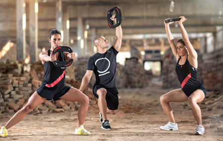 stretching condition: Group of young sporty people exercise with weights in unfinished building
