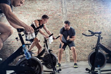 fitness hombres: los jóvenes aptos en la bicicleta de ejercicio