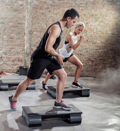 gimnasia aerobica: Hombres deportivas entrenan jóvenes mujer se mueve en de pasos