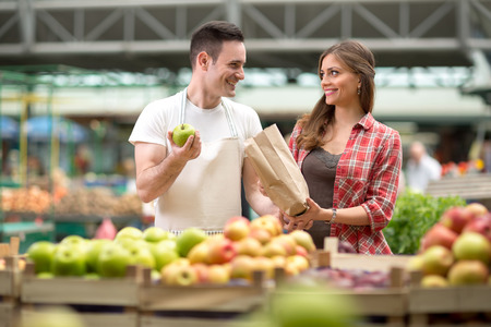apple paper bag: smile salesman presentation produces at the market Stock Photo