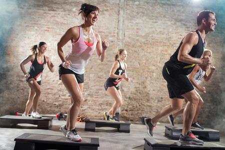 gimnasia aerobica: la gente positiva y alegre que hace ejercicio en steppers
