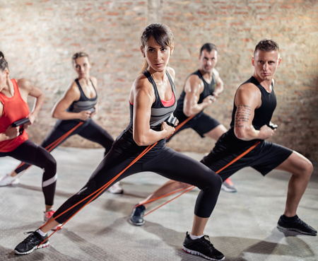 Group of young people exercising muscles with resistance band, health and stronger body Stock Photo