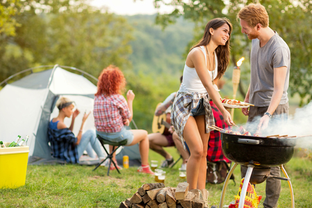 Male and female lovingly look each other while baked barbecue in green nature Stock Photo