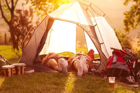 Couple sleeping in tent at early morning sun Stockfoto