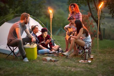 campamento: La socialización de los jóvenes delante de la tienda con la cerveza, guitarra y tambores en la noche