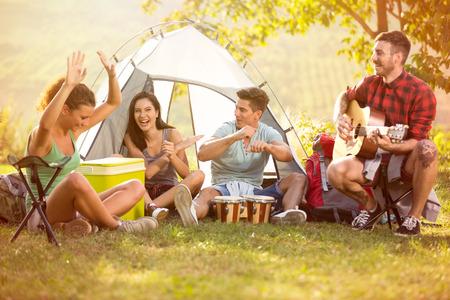一群笑着的年轻人在露营旅行中享受着鼓声和吉他的音乐