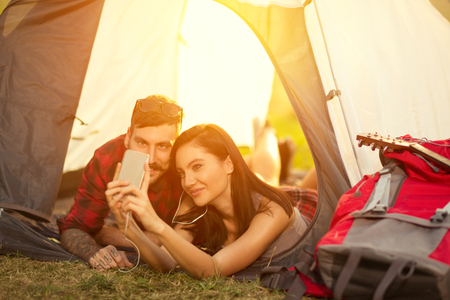 intimately: Campers self portrait, woman and man smiling in tent, happy people having fun. Stock Photo