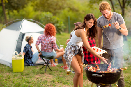 Young brunette with boyfriend serving on plate barbecue to their friends in campground Stock Photo