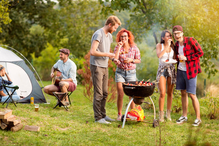 Guys and lassies feed each other with skewers in outing in wood Stock Photo