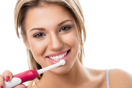 Smiling girl with electric toothbrush, brushing teeth