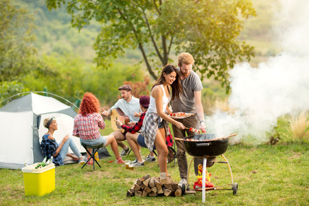 Young female and male couple baking barbecue in nature Imagens