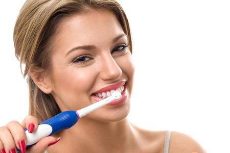 higiene bucal: Mujer hermosa joven que aplica sus dientes sanos, higiene bucal