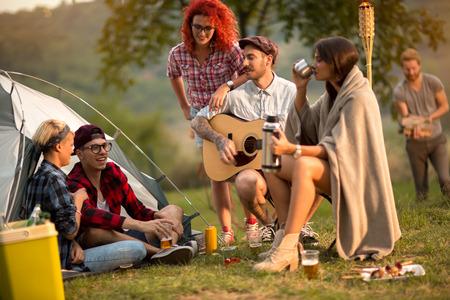 socializando: Mujeres y hombres de socialización en la puesta del sol en el campo en la naturaleza