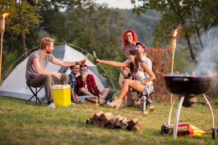 campground: Guys and lassies tapping with bottles and glasses of beer in campground