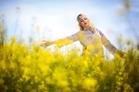 oilseed: Beautiful woman in oilseed rape flowers, yellow field