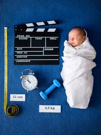 personal data: newborn baby lying on blue blanket with symbolic personal data of birth Stock Photo